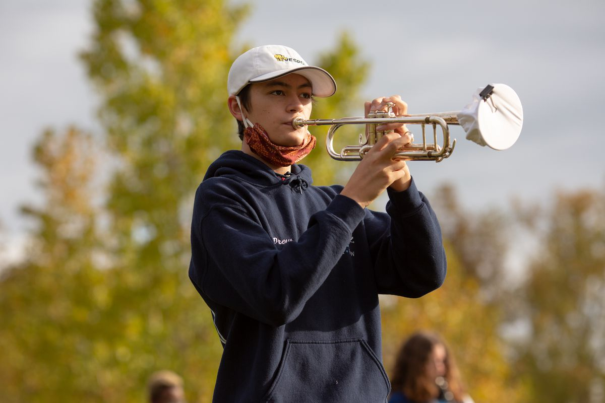 A student with a red mask below his chin plays a trumpet outside. Trees are in the background.