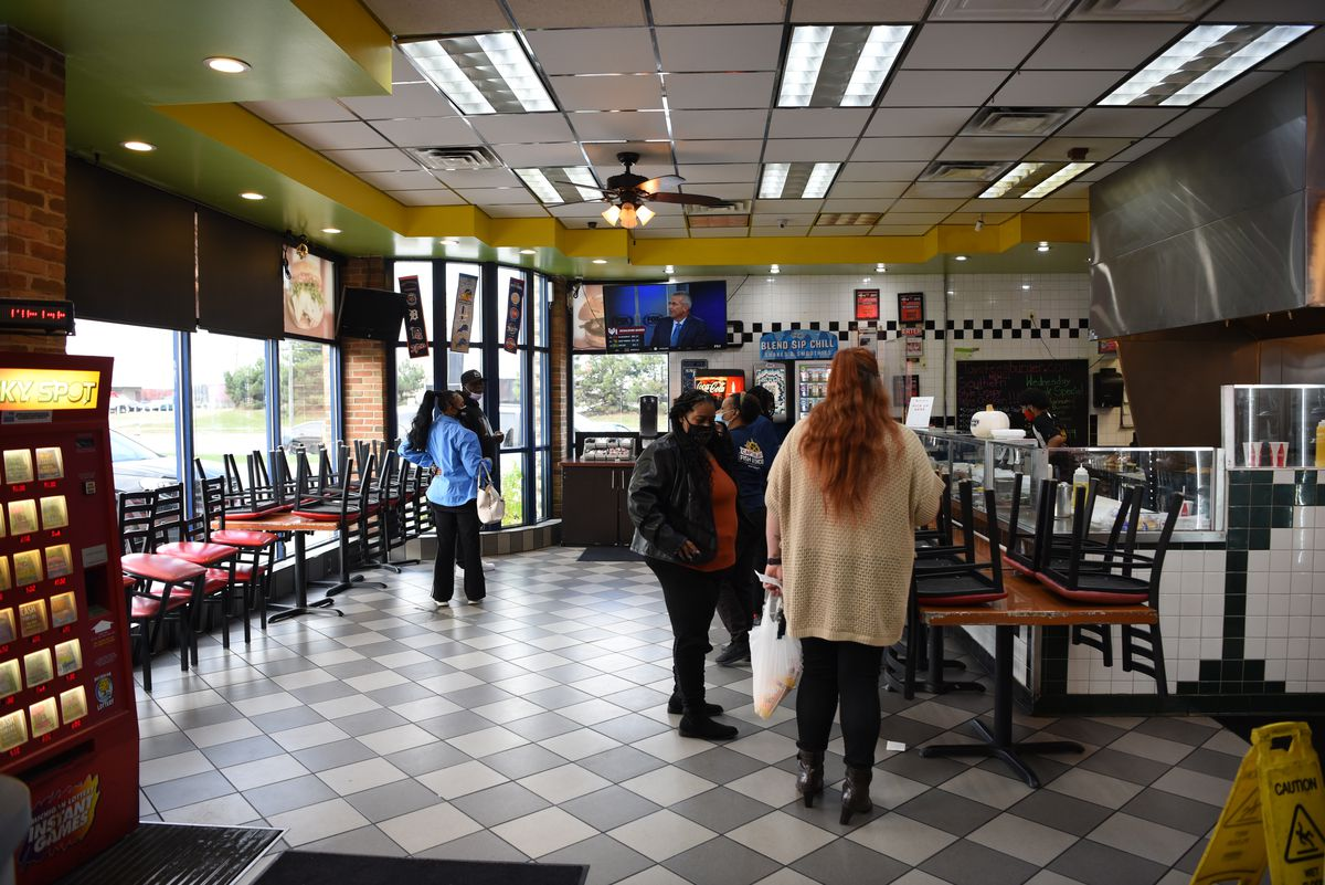 Customers gather inside the gas station location of Taystee's Burgers in Dearborn where chairs and tables are stacked up.