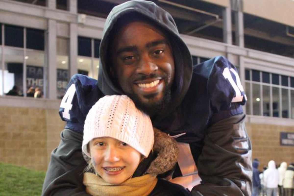 Mike Wallace standing outside of Beaver Stadium with a THON child that is now cancer-free.