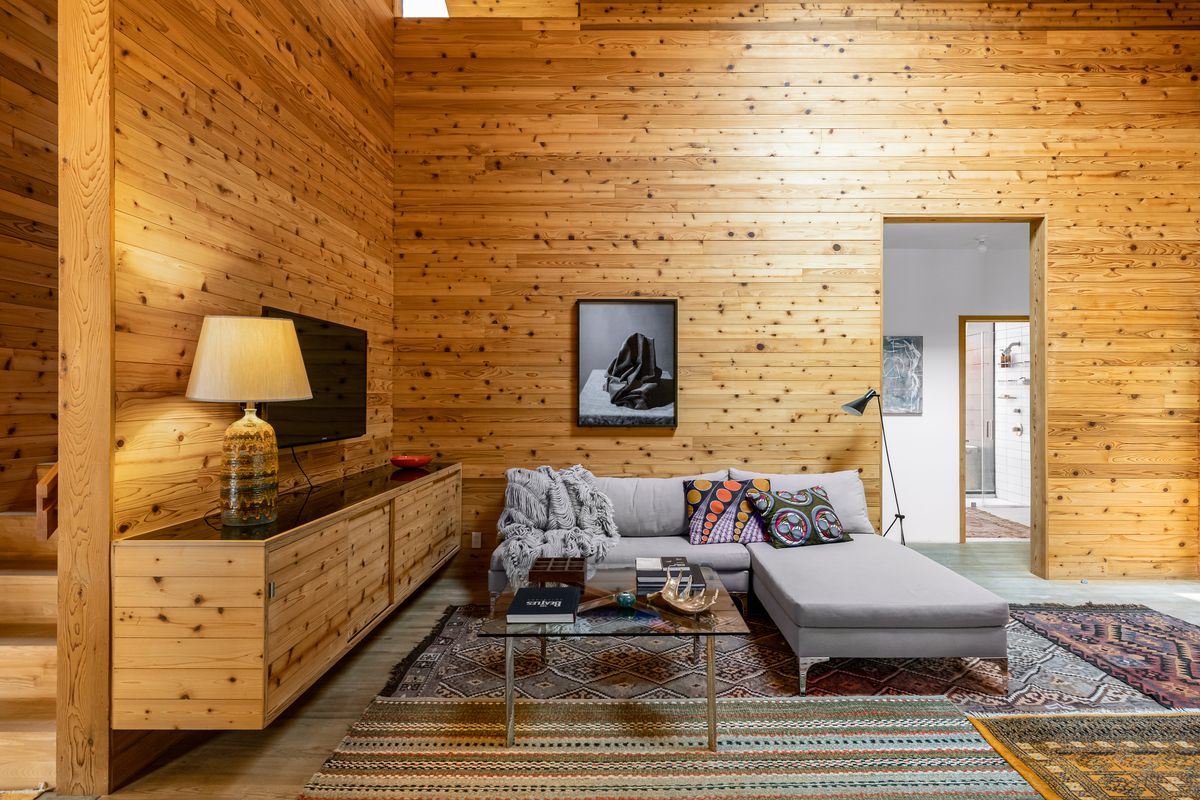 A living room with pine-wood walls and cabinets.