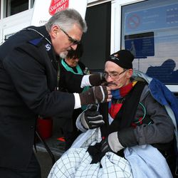 Doug Holladay, a former Salvation Army worker who is fighting terminal lung cancer, rings a bell for donations a final time in Riverdale, Thursday, Dec. 5, 2013. Longtime friend Raymond Young of the Salvation Army helps Doug with his oxygen tube.