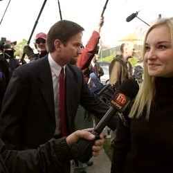 Amanda Smart, a cousin of Elizabeth Smart, talks with the media prior to a Mormon Church service in honor of the 15-year-old girl Sunday, March 16, 2003, in Salt Lake City. Dave Smart, an uncle to Elizabeth, slips through the crowd at center. Elizabeth and her immediate family did not attend, opting to stay at home instead.