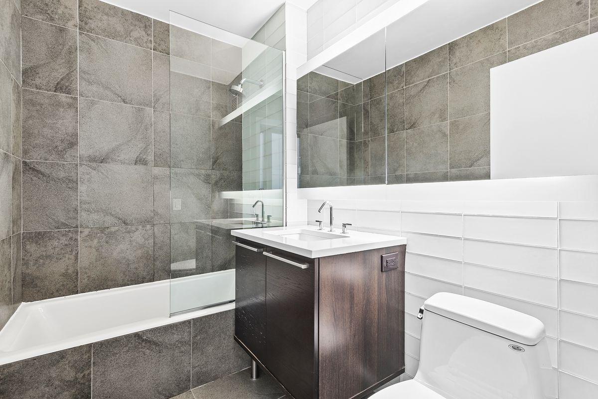 A bathroom with smoky gray tiles.