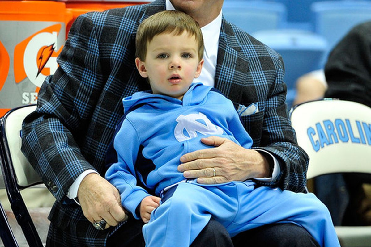 Roy Williams sits with his grandson, Aiden Williams, before a game against the Virginia Cavaliers at the Dean Smith Center on February 11, 2012. North Carolina won 70-52.