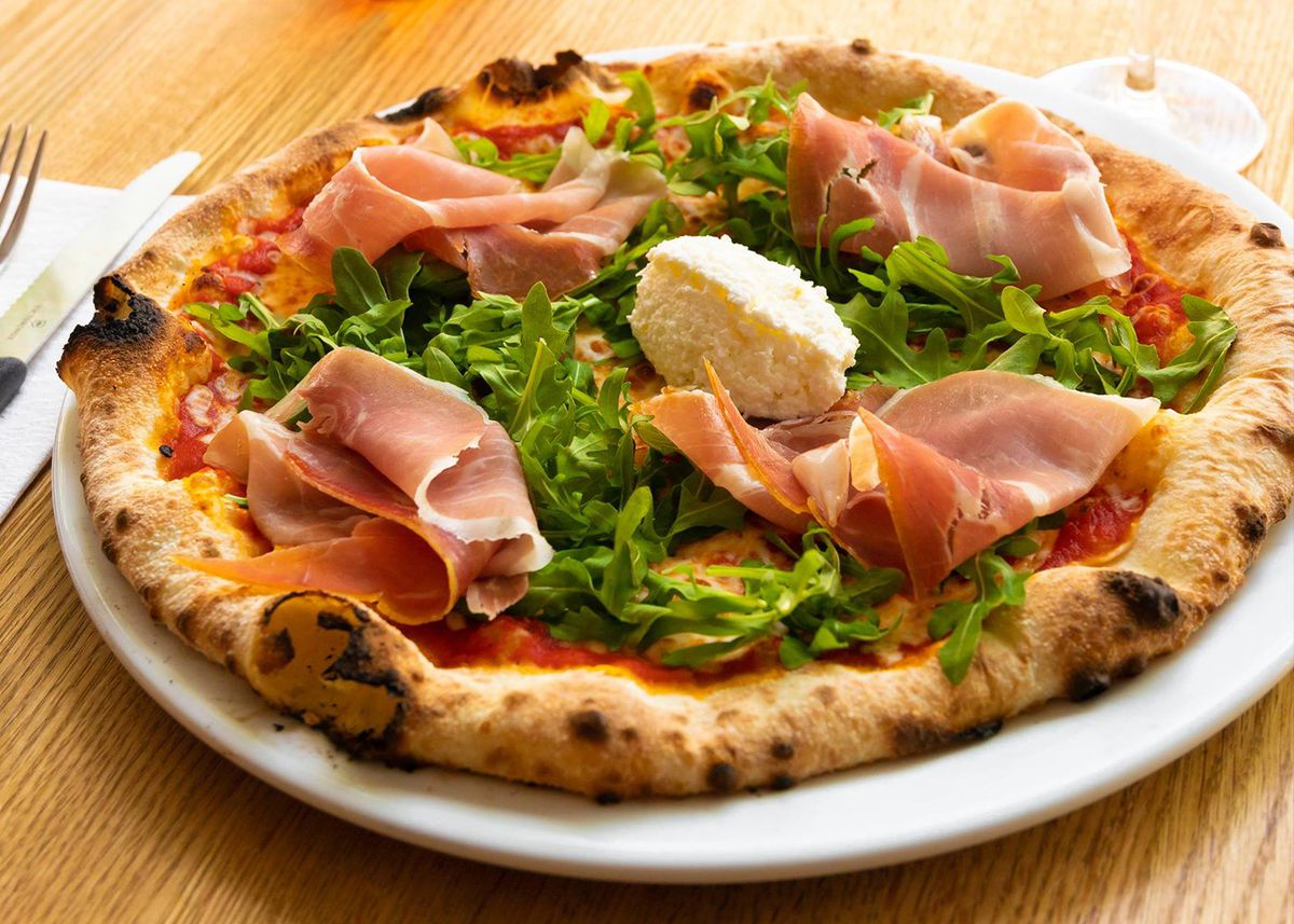 A Neapolitan-style pizza with a puffy crust, a tomato base, and ham and arugula toppings.