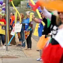 Teachers at Farr West Elementary in Farr West, Weber County line the street in front of the school to wave at students with scarves as they and their parents drive by on the last day of classes on Friday, May 15, 2020.