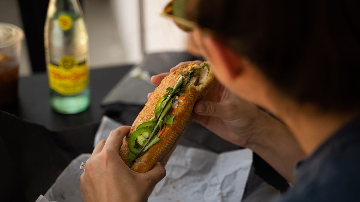 Two hands hold a banh mi sandwich with a bite removed.