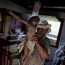 A man shows a damaged crucifix at an earthquake damaged church in Bellavista, Costa Rica, Thursday, Sept. 6, 2012.  A powerful, magnitude-7.6 earthquake shook Costa Rica and a wide swath of Central America on Wednesday.