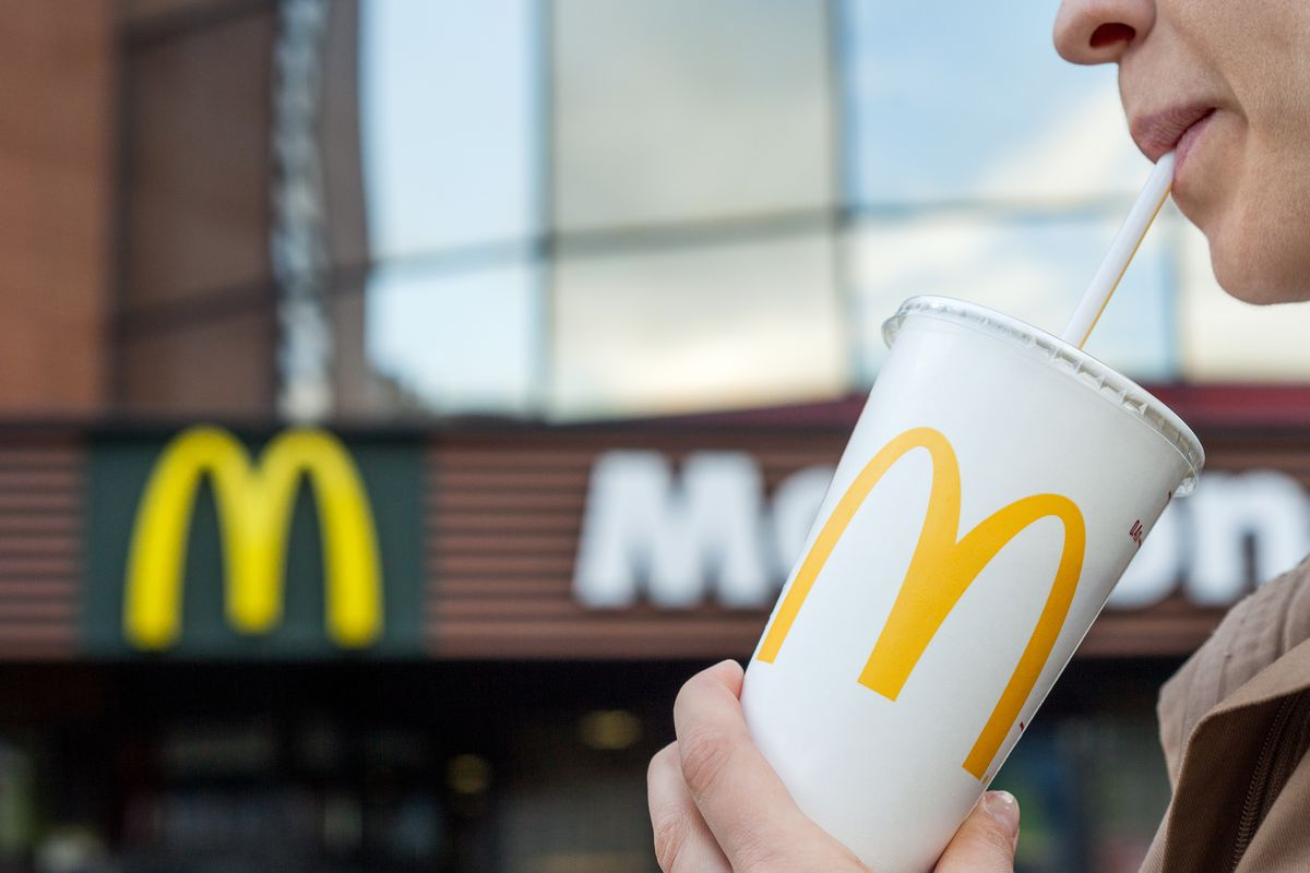A woman drinking from a McDonald's beverage with a straw in it, with a McDonald's store in the background.