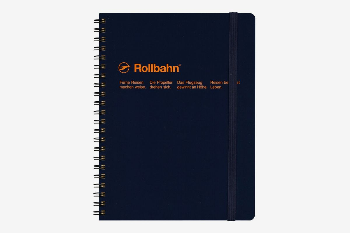 Black wired notebook with orange text on cover.