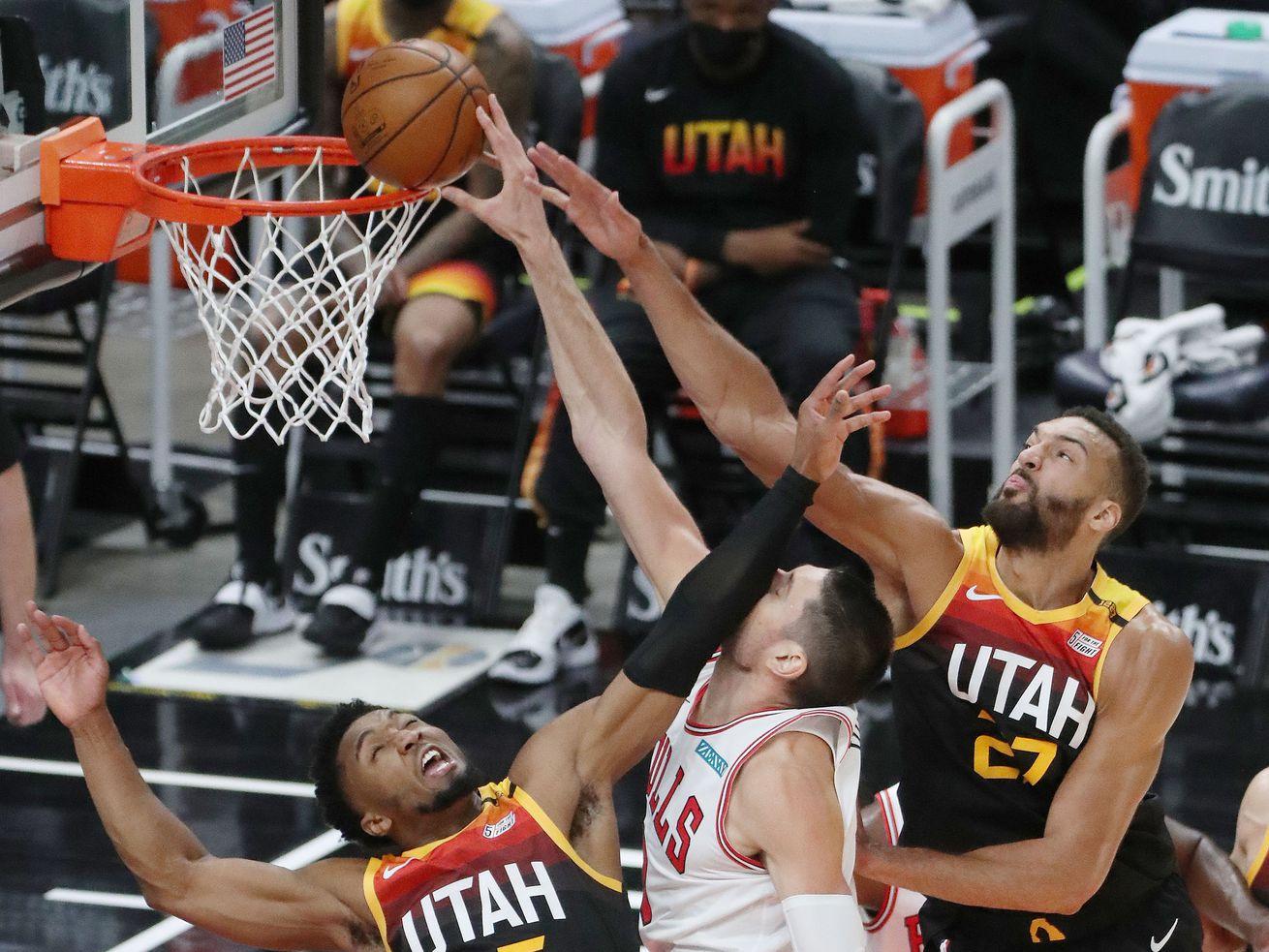 Utah Jazz guard Donovan Mitchell (45) and Utah Jazz center Rudy Gobert (27) defend Chicago Bulls center Nikola Vucevic (9) in Salt Lake City on Friday, April 2, 2021.