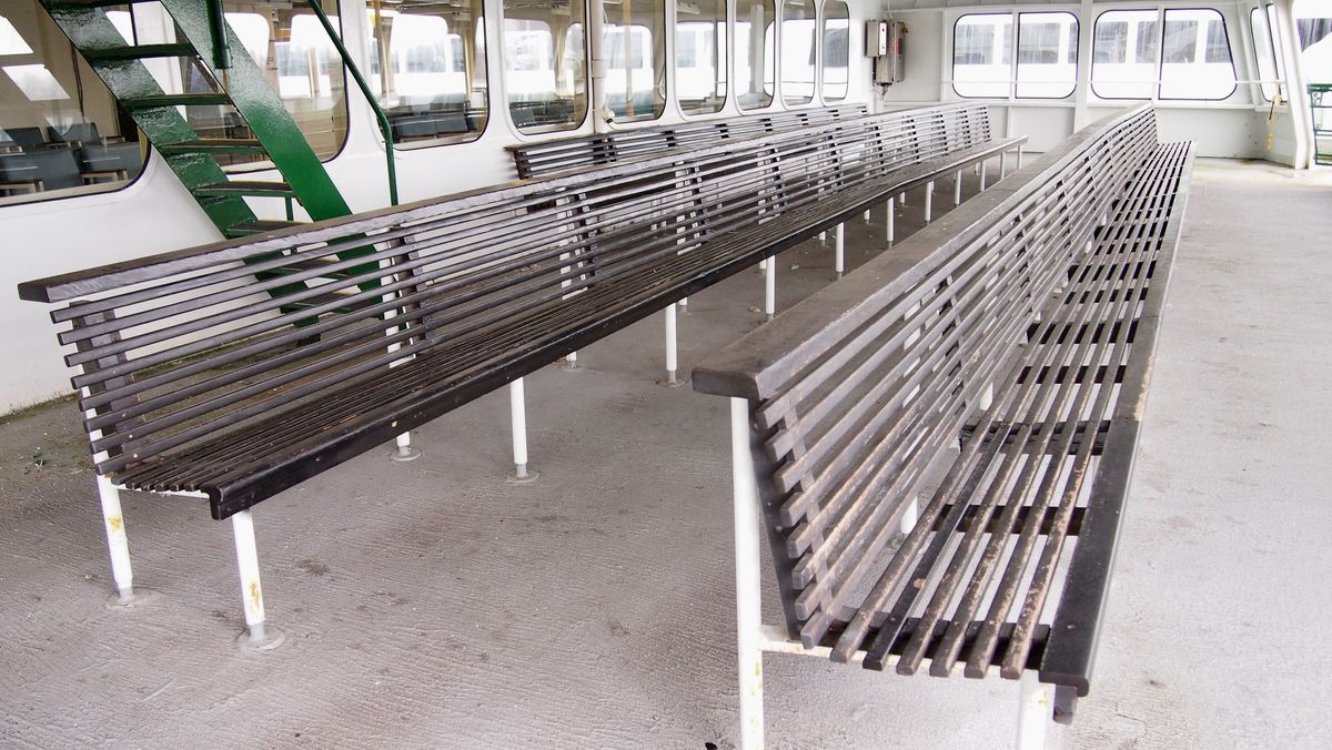 Two long, wooden benches. Interior windows behind the benches lead into the ferry, with exterior windows at the end of the rows. A green ladder sits between the interior windows and the benches.