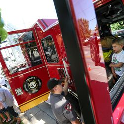 Cadet John Strate talks to Drake Orcutt, 4, while the Salt Lake City Fire Department shows off its two new ladder trucks at Smith's Ballpark in Salt Lake City on Tuesday, June 27, 2017.