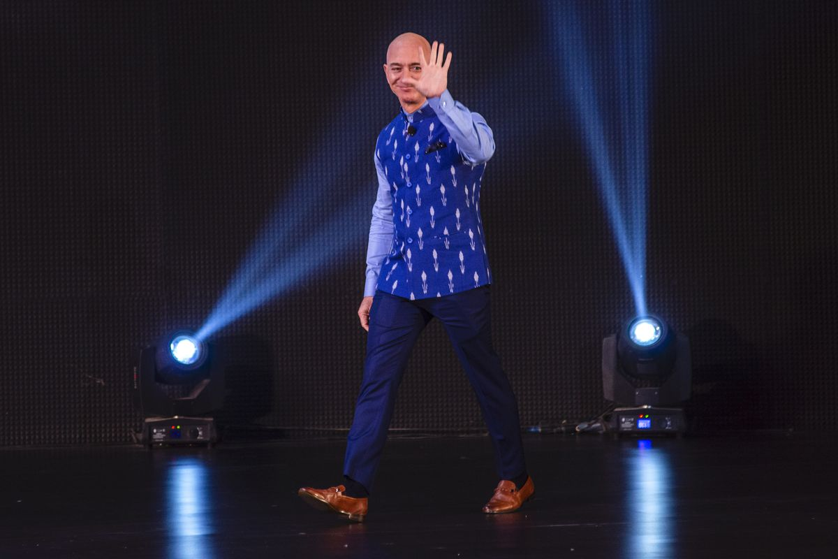 Amazon CEO Jeff Bezos walks across a stage