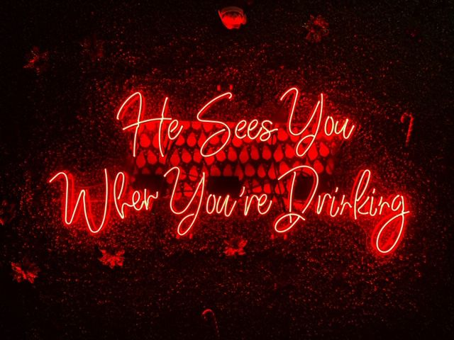A neon sign that says He sees you when you're drinking