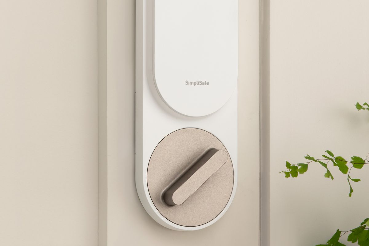 A SimpliSafe smart lock above a door knob on a white door with a green fern nearby.