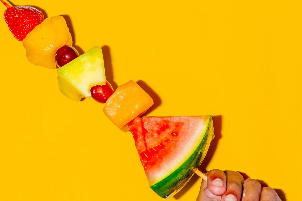 A hand holding a fruit salad on a stick against a yellow background