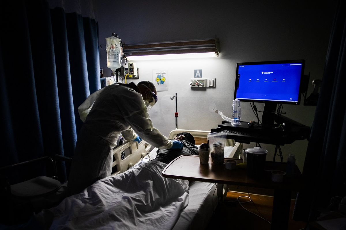A health care worker leans over a patient in a darkened hospital room.