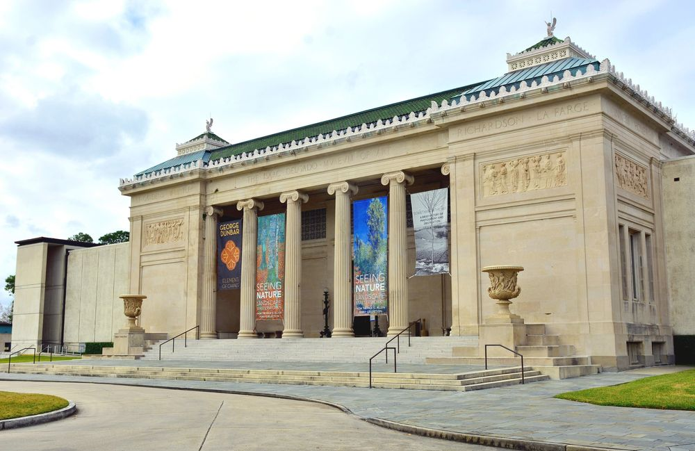 The exterior of the New Orleans Museum of Art. The facade is tan with columns near the entrance.