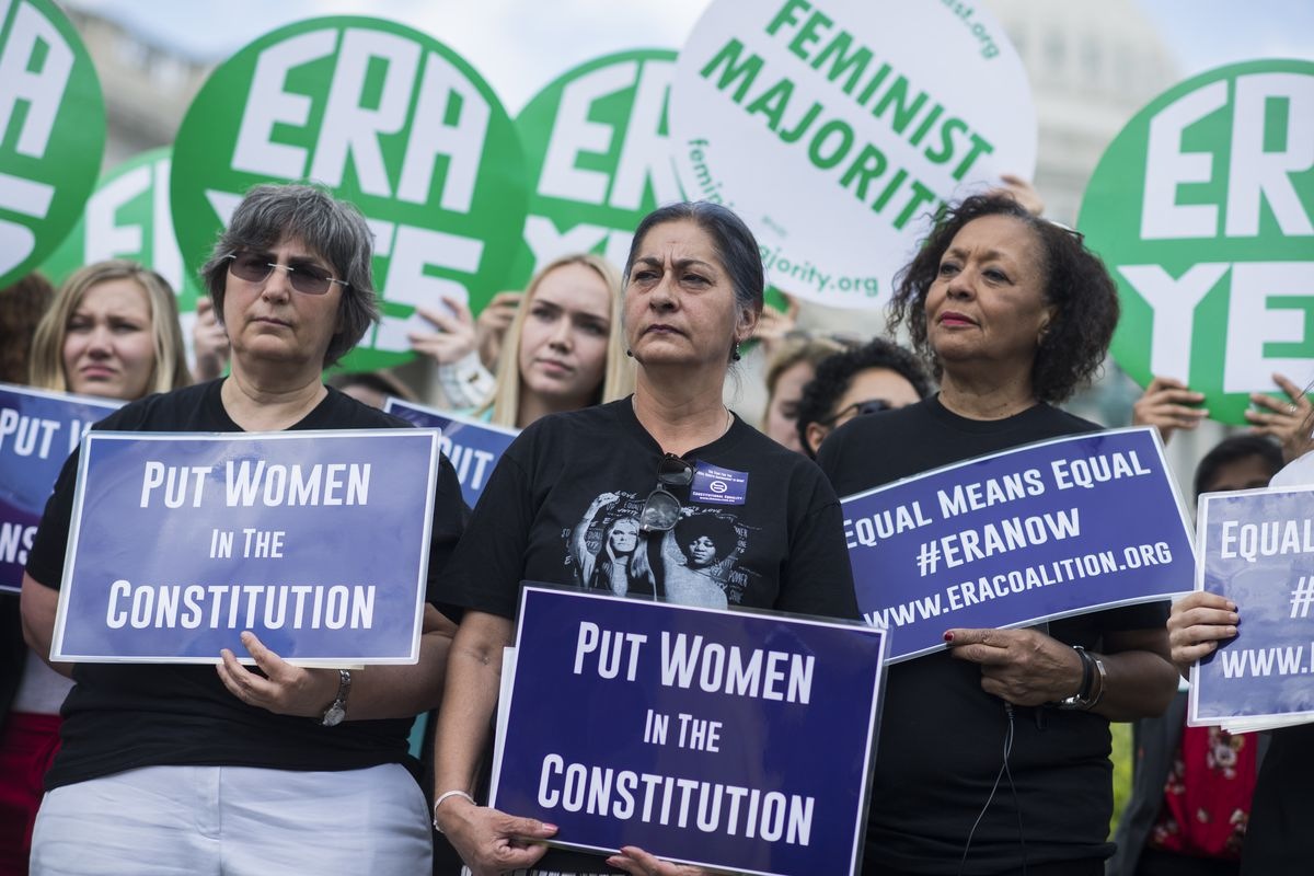"""Demonstrators hold signs reading """"Put women in the Constitution,"""" """"Equal means equal #ERANow"""" and """"ERA Yes."""""""