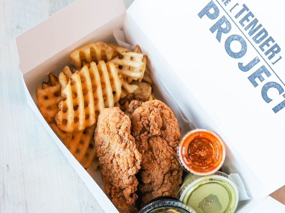 Box of chicken tenders with waffle fries and sauces