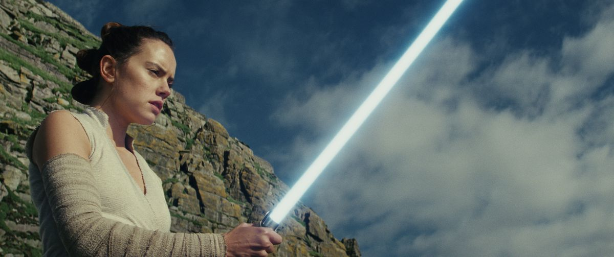 Rey holding a lightsaber
