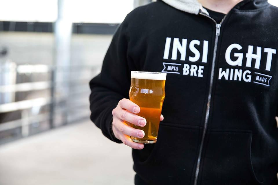 A man in an Insight Brewing hoodie holding a pint of beer