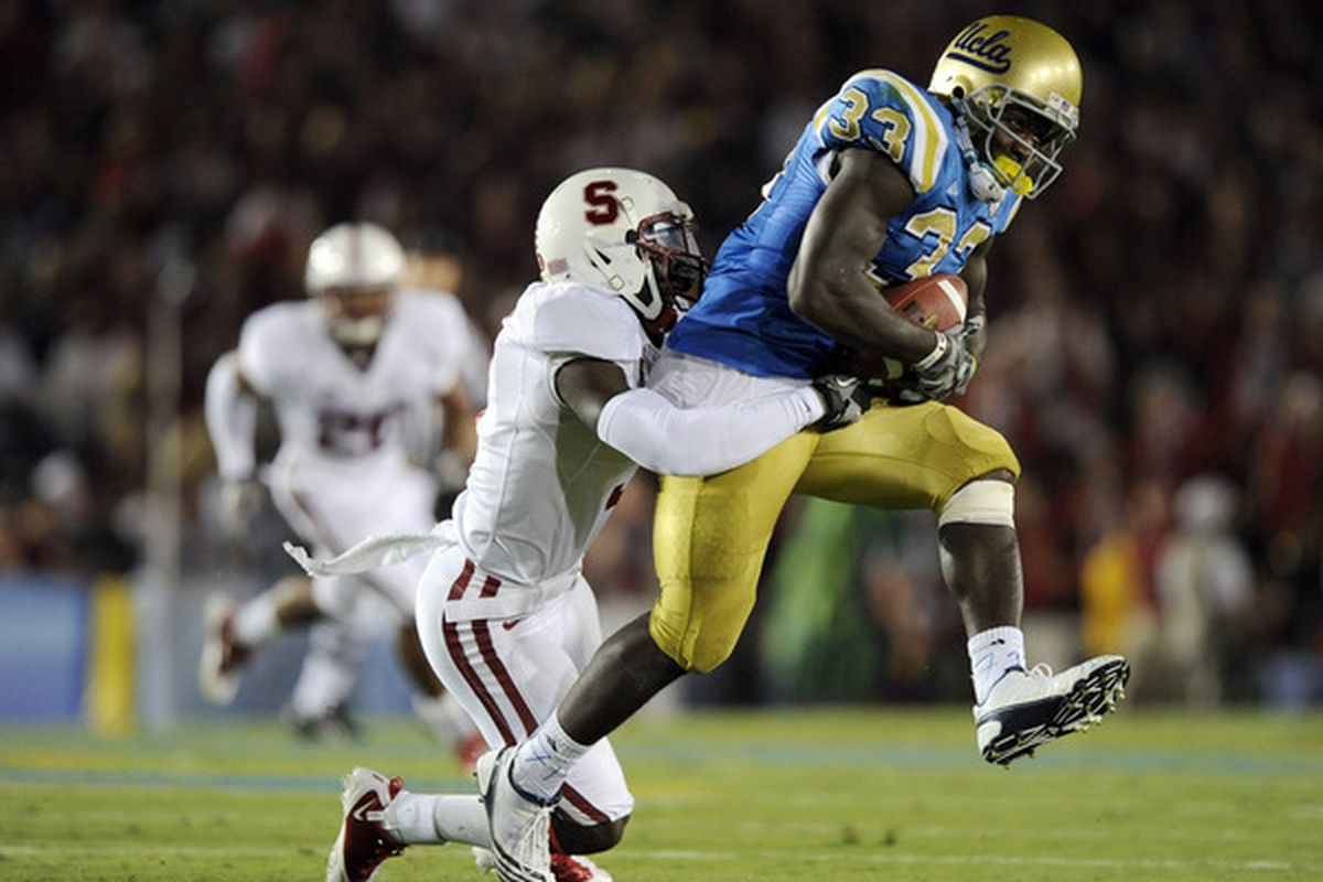 PASADENA CA - SEPTEMBER 11:  Derrick Coleman #33 of UCLA is tackled by Michael Thomas #3 of  Stanford during the first quarter at the Rose Bowl on September 11 2010 in Pasadena California.  (Photo by Harry How/Getty Images)