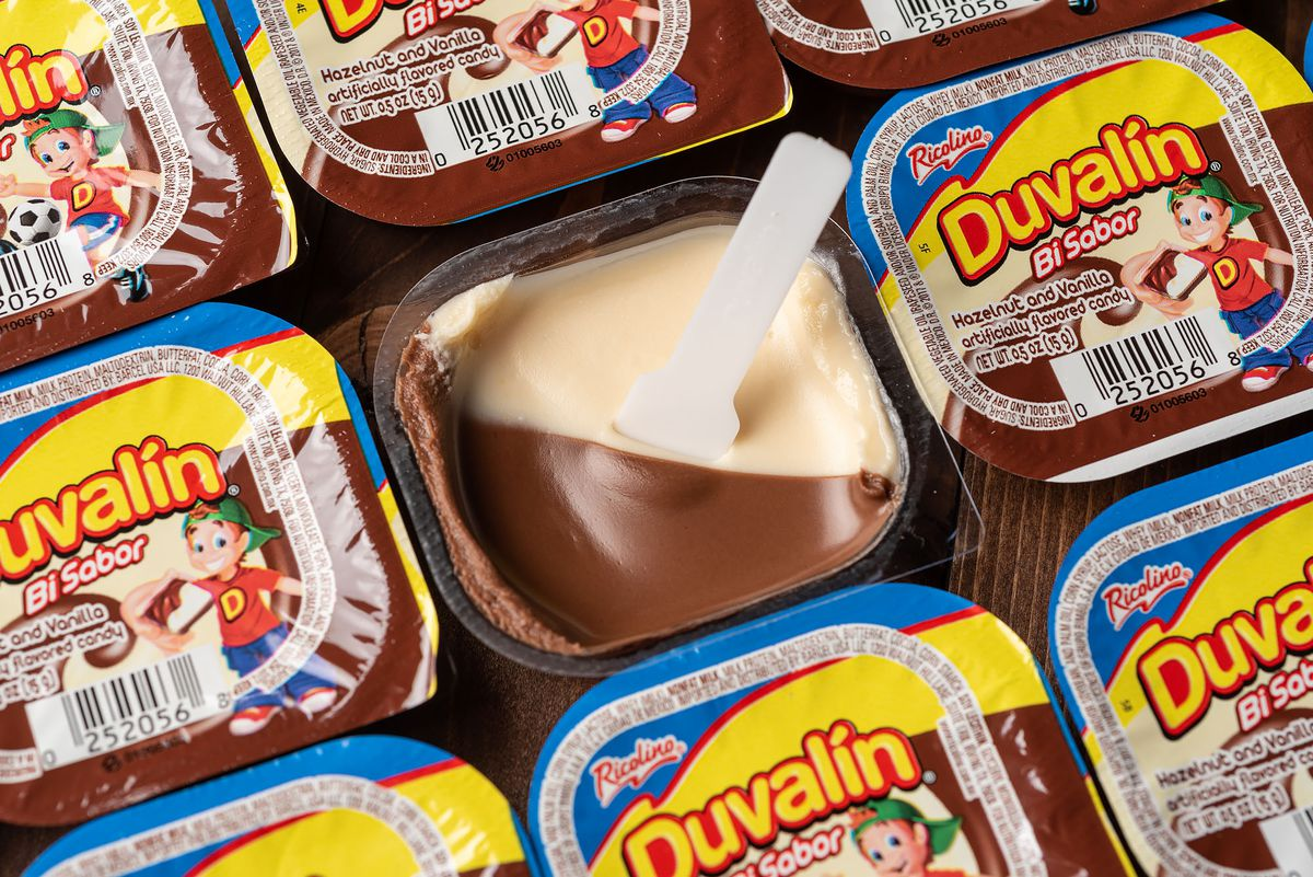 An open package of Duvalín with a plastic spoon surrounded by closed Duvalíns