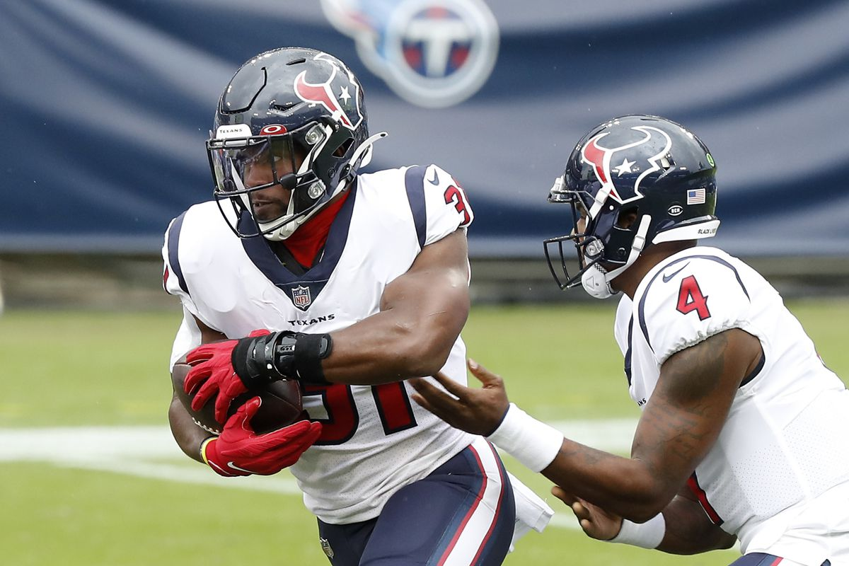 Running back David Johnson of the Houston Texans takes the hand off from quarterback Deshaun Watson in the first quarter against the Tennessee Titans at Nissan Stadium on October 18, 2020 in Nashville, Tennessee.
