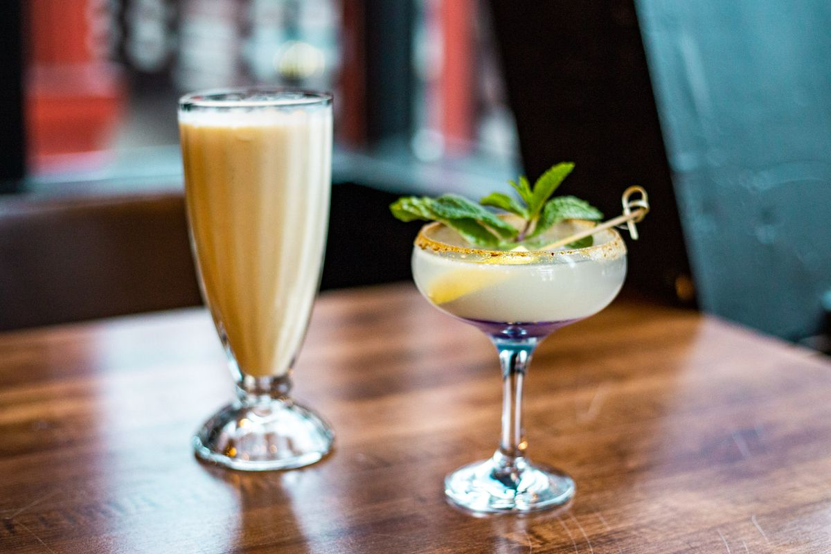 A glass of eggnog lassi on the left, and a gin cocktail on the right on a wooden bar.