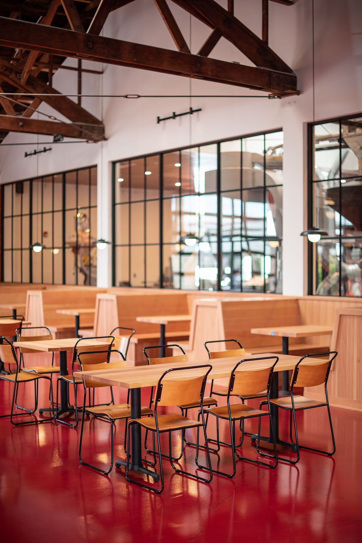Wooden booths and tables inside a new cafe with red floors.