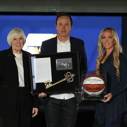 Gail Miller, Qualtrics CEO Ryan Smith and his wife, Ashley Smith, pose for a photograph at Vivint SmartHome Arena in Salt Lake City on Wednesday, Oct. 28, 2020.