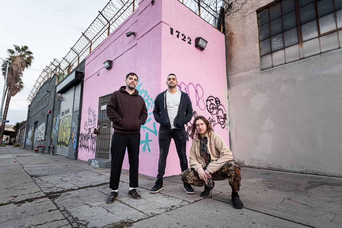 Three guys stand low in front of their pink music venue in Downtown LA.