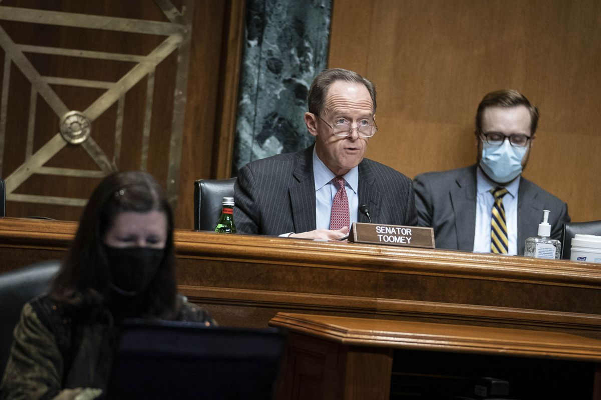 Pat Toomey seated at a desk during a hearing.