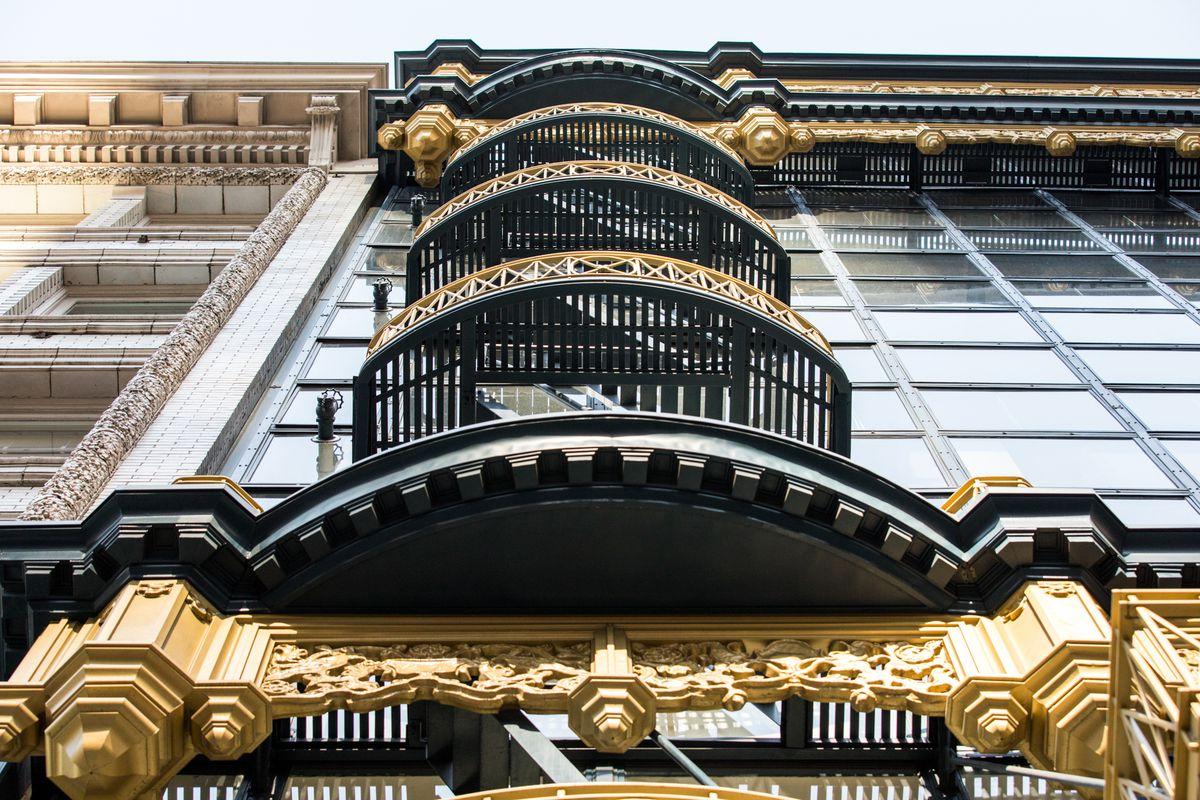 Vertikale Aufnahme der Glaswand mit den goldfarbenen Metall- und Eisenfenstern.  Ebenfalls zu sehen ist einer von mehreren Balkonen, die als Feuerleiter dienen.  Sehr kompliziert und detailliert.