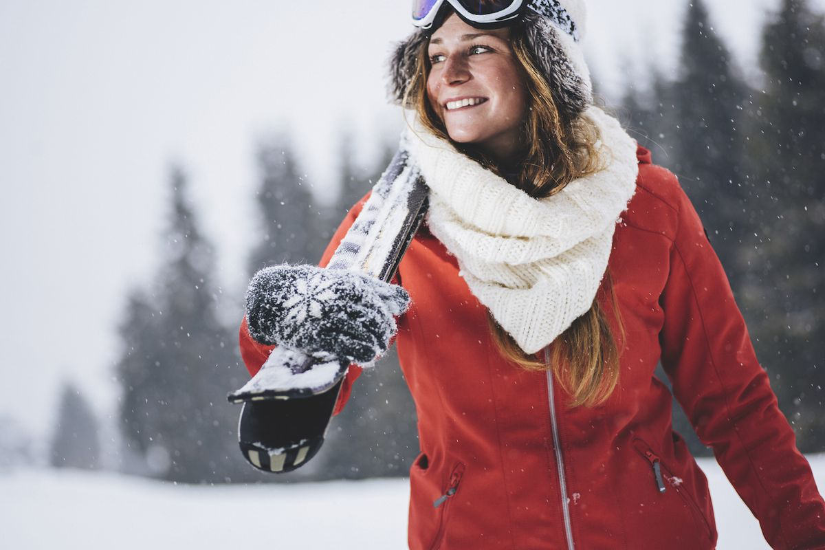 A woman carrying a snowboard in a heavy coat and scarf