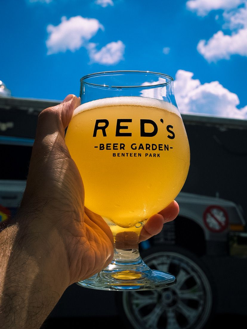 Hand holding a hazy IPA up to the sun set against blue skies and puffy white clouds in goblet branded with Red's Beer Garden, Benteen Park