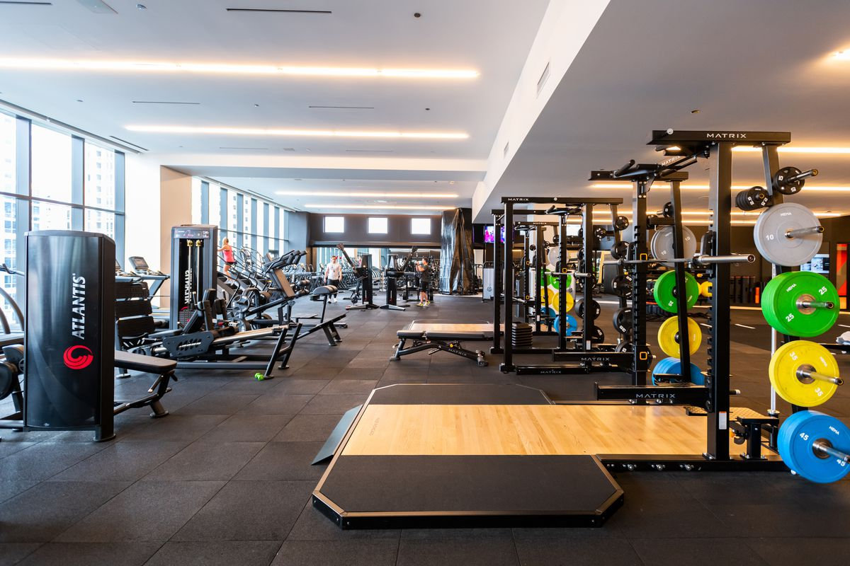 A sprawling workout area with a black rubberized floor and dozens of exercise machines.
