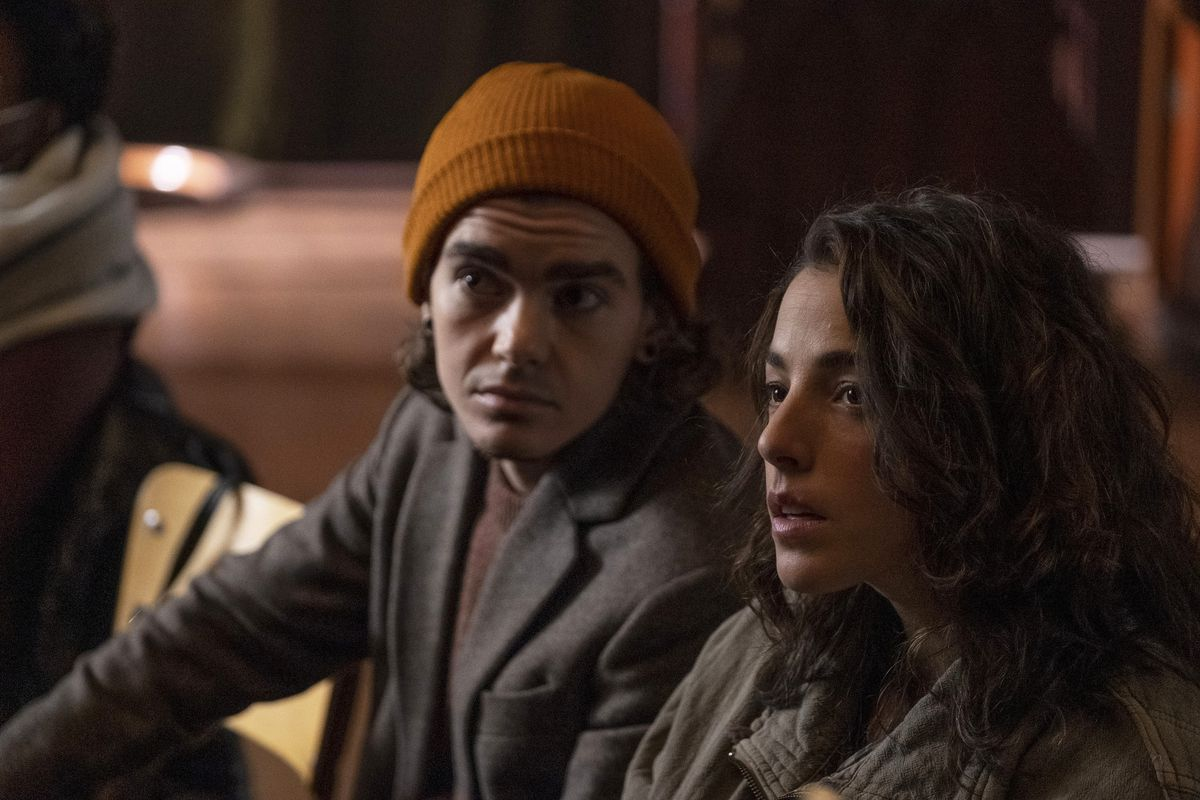 Elliot Fletcher as Sam and Olivia Thirlby as the hero sit together on a couch in Y: The Last Man