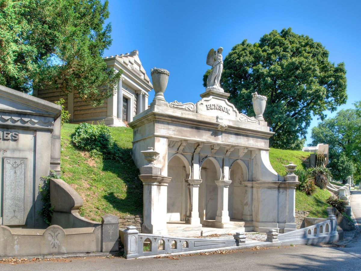 The Laurel Hill Cemetery in Philadelphia. There are multiple above ground graves. The grave in the foreground is white with columns and a statue on top.