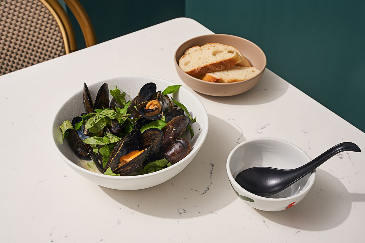 Three white bowls sit on a white table, one filled with mussels and green herbs, another filled with slices of bread, and a third with a black spoon