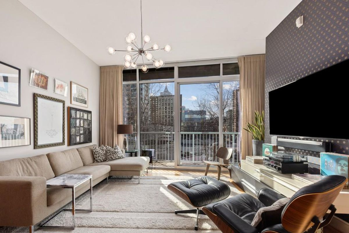 A condo with a beige couch at left and large windows overlooking a balcony with a big city beyond.