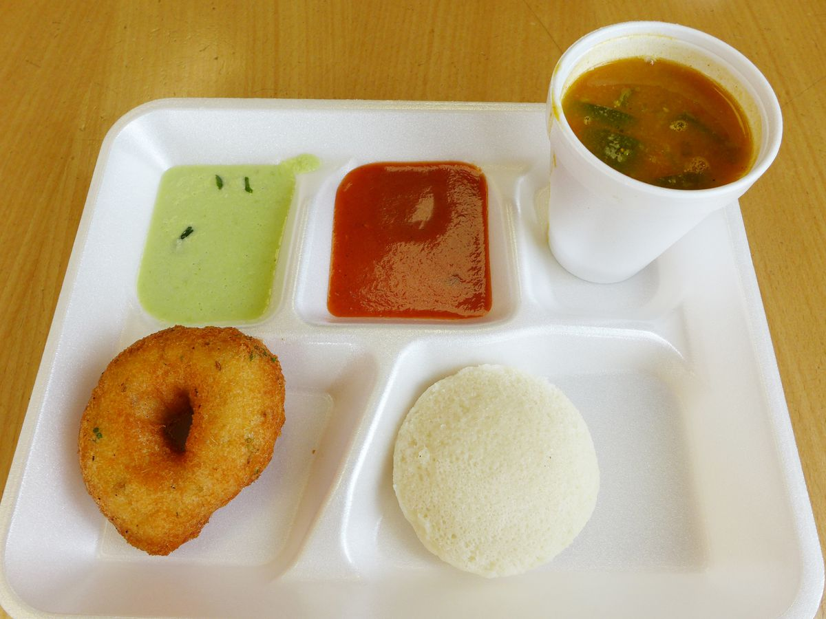 A round brown pastry, a white saucer shaped pastry, a soup in a cup, and green and red sauces, most in compartments.
