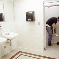 Eric Richardson prepares to shower in the men's restroom of the facilities building at Utah State University.