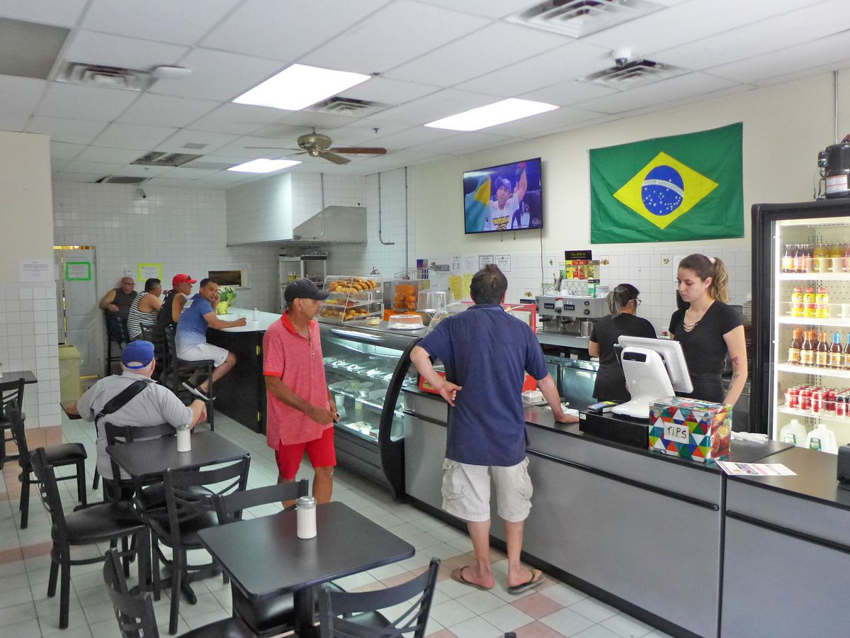 An informal cafe with several black tables and chairs on one side and a counter with a few customers crowded along it, and a flag of Brazil on the wall above...
