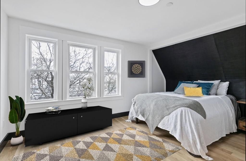A bedroom with a bed, three windows, and the ceiling kind of slopes in over the bed.