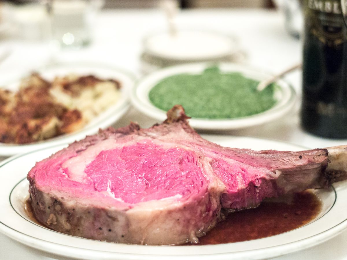 Medium rare prime rib on a white plate with creamed spinach in the background.