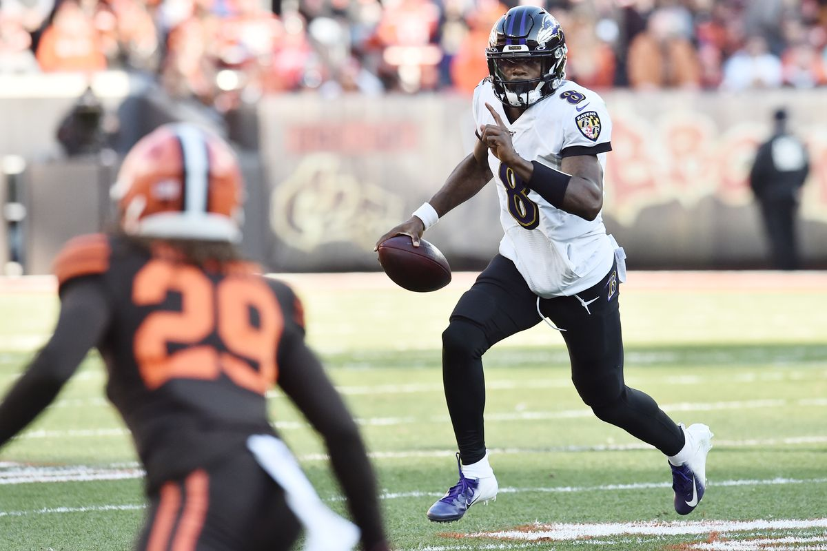 Baltimore Ravens quarterback Lamar Jackson runs the ball as Cleveland Browns defensive back Sheldrick Redwine defends during the second half at FirstEnergy Stadium.
