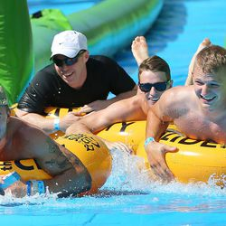 Jon Turcotte, Tyler Gibbs, Alec Eckert, and Kelvin Shank have fun as they and hundreds of others enjoy the sun and water Saturday, Aug. 22, 2015, as they participate in Slide the City, in Salt Lake City.